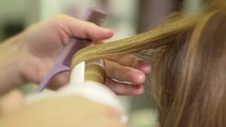 ヘアアイロンで髪を巻く美容師