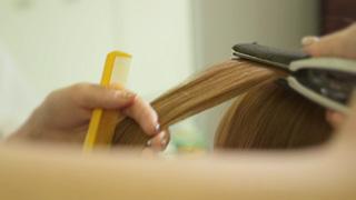 ヘアアイロンで髪をストレートにする美容師
