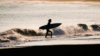 砂浜を歩くサーファー